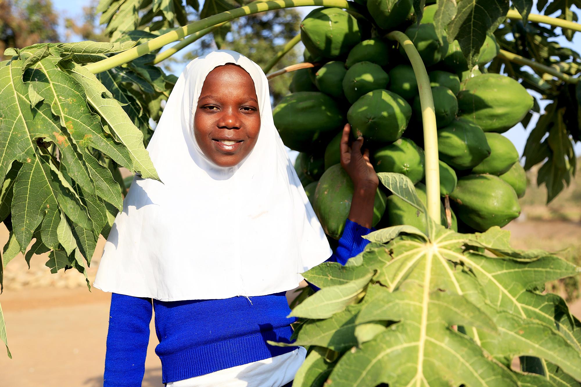 Fatuma Yasin som med stöd av Vi-skogens arbete kämpar mot torka och översvämningar - genom att plantera träd. På bilden står Fatuma framför ett papayaträd.